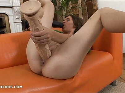 Hungry brunette sucks on a big dildo as the other fills her